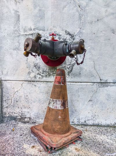Fire hydrant against wall in city