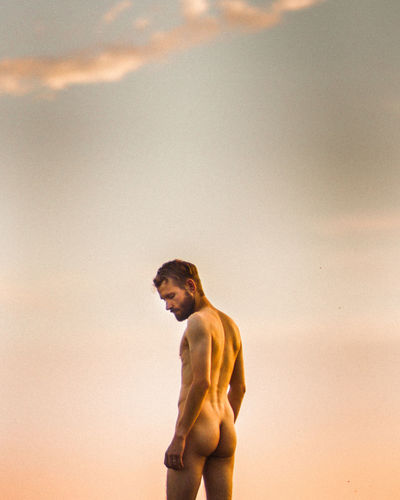 Rear view of naked man standing against sky during sunset