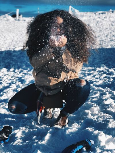Young woman playing on snow field during winter