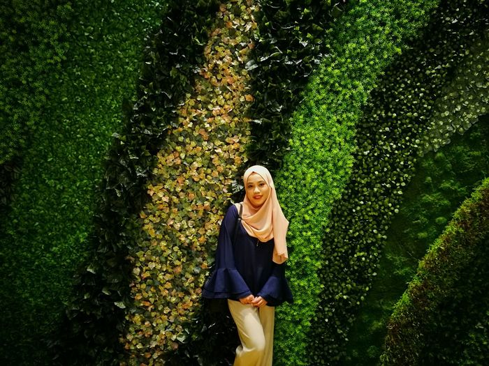 Portrait of woman in hijab standing by plants at park
