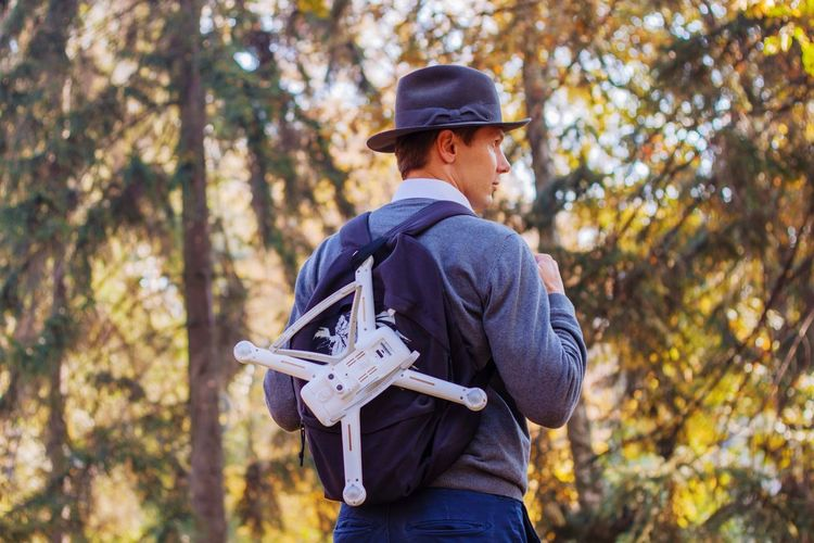 Man with drone standing against trees in forest
