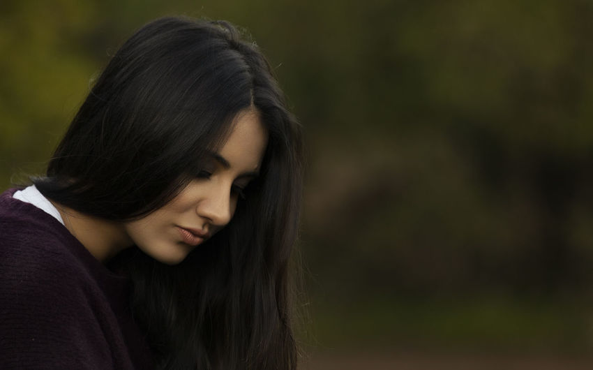 Melancholic pretty girl with straight hair in the outdoors