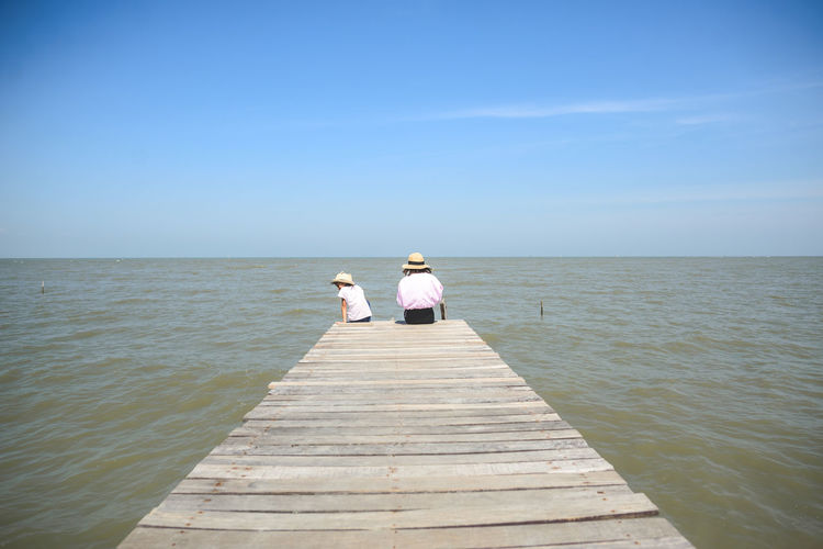 Rear view of woman with child sitting on pier over sea