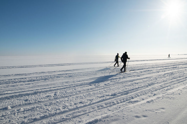 People skiing on snow covered land against sky