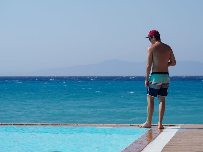 Rear view of shirtless man standing by a infinity pool