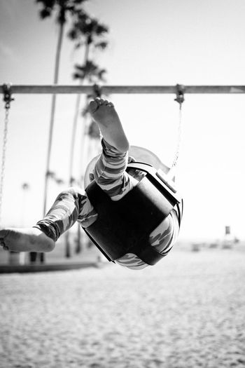 Low section of child swinging at playground against sky