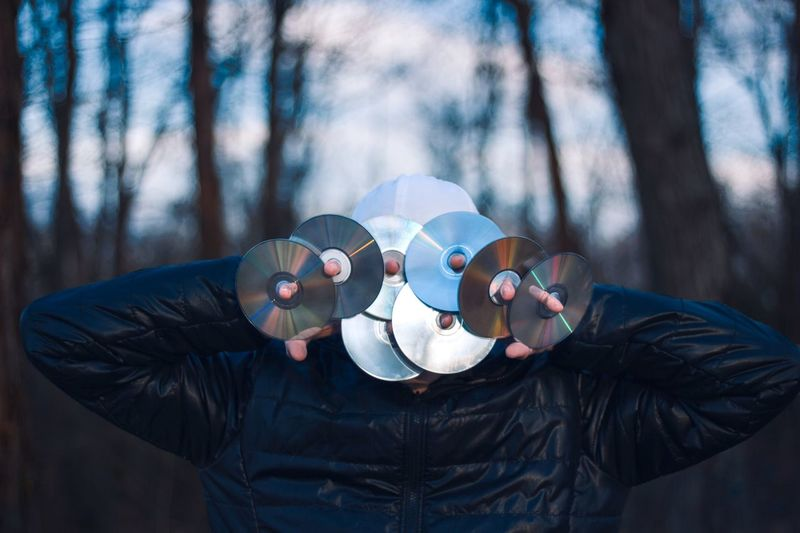 Man holding compact discs against his face in forest