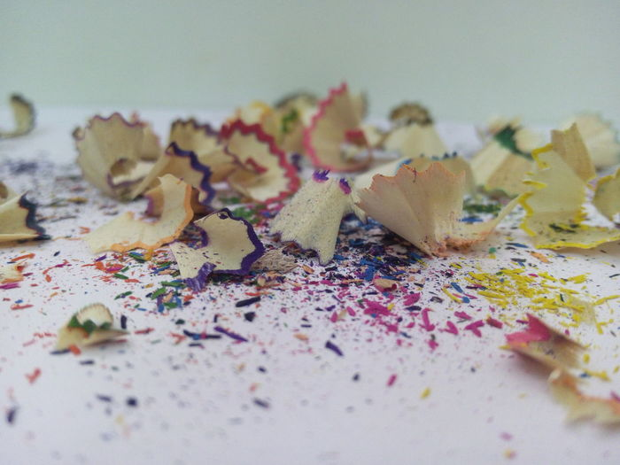 Close-Up Of Colored Pencil Shavings On Table