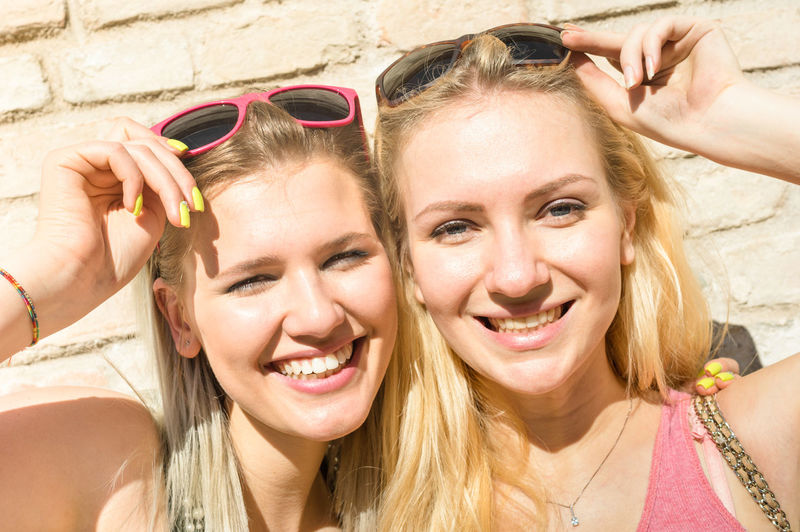 Portrait Of Cheerful Female Friends Wearing Sunglasses