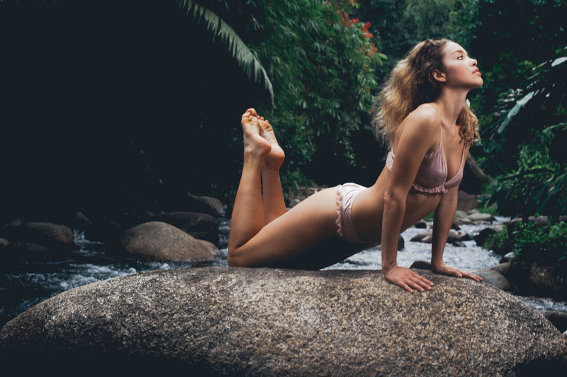 Full length of young woman wearing bikini while exercising on rock at forest
