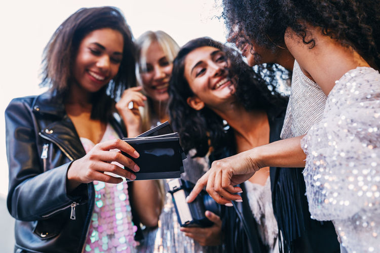 Cheerful friends holding photographs
