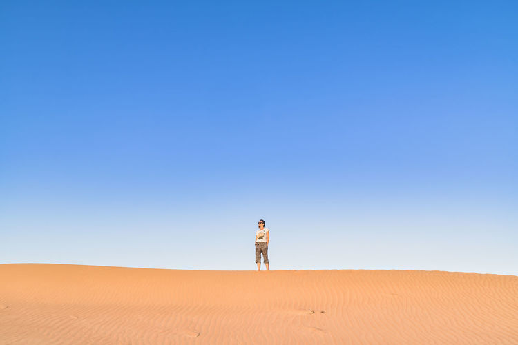 Woman standing on desert against clear blue sky