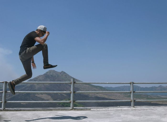 Full Length Side View Of Young Man Jumping At Observation Point With Gunung Batur In Background