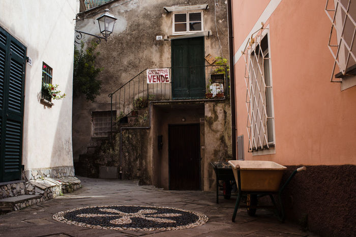 Liguria,Italy Trolley Architecture Building Exterior Built Structure Cart Cobblestone Courtyard  Day Door Medieval No People Old Ornaments Outdoors Pavement Streetlights Town Walls Windows