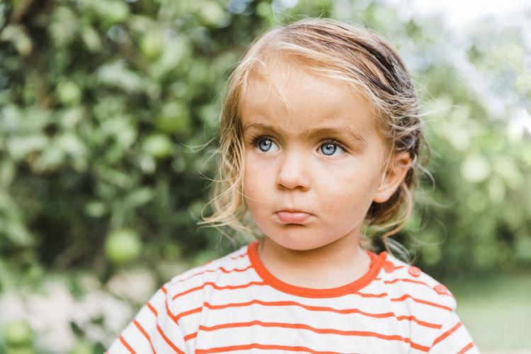 Cute girl looking away against trees
