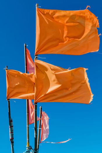 Low angle view of orange flags waving against clear blue sky