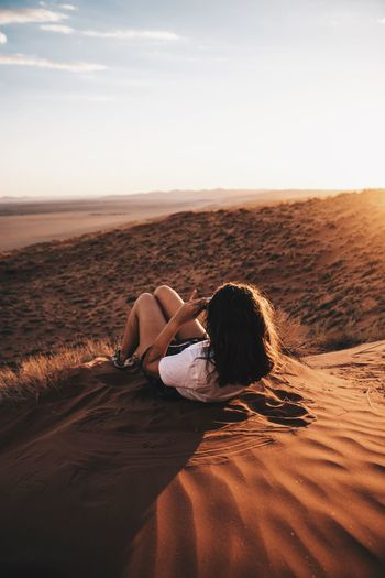 Rear view of young woman lying on sand at desert against sky