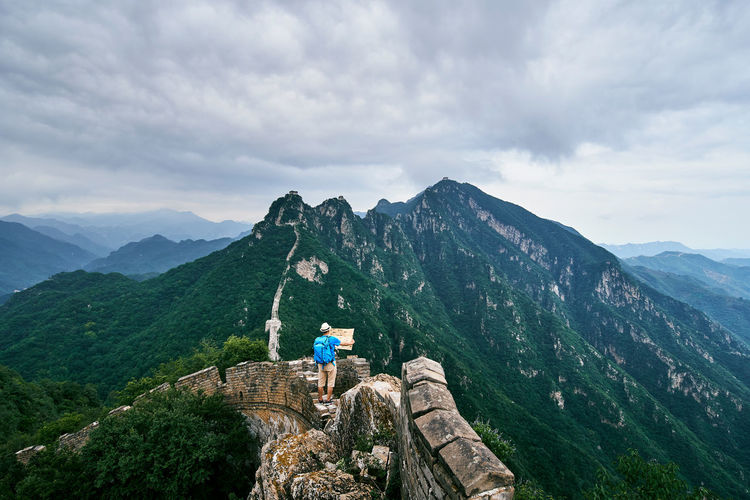 High angle view of man holding map while standing on great wall of china