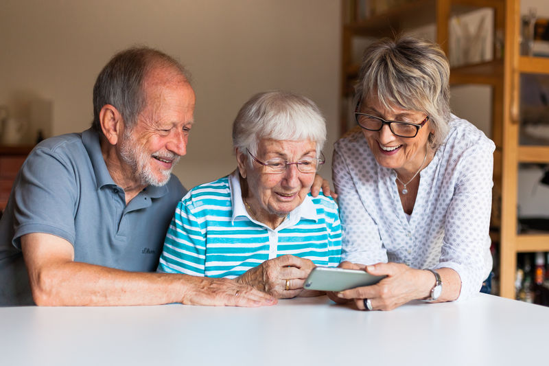 Senior People Using Mobile Phone At Table In Home