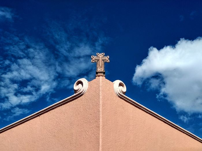 Low angle view of cross and building against blue sky