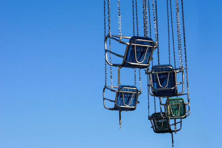 Empty seats of chain swing ride against clear sky