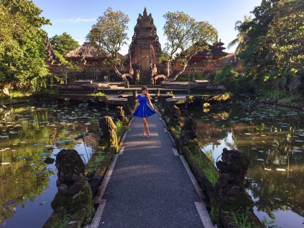 Architecture Bali Building Exterior Built Structure Cultures Day Famous Place Girl Horizontal Symmetry Human Settlement Leading Morning Outdoors Place Of Worship Pond Religion Residential District Sculpture Spirituality Statue Temple Temple - Building Tradition Ubud Vanishing Point