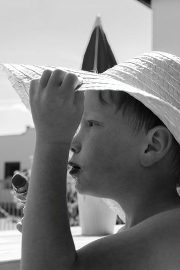 Side View Of Boy Looking Away While Holding Hat