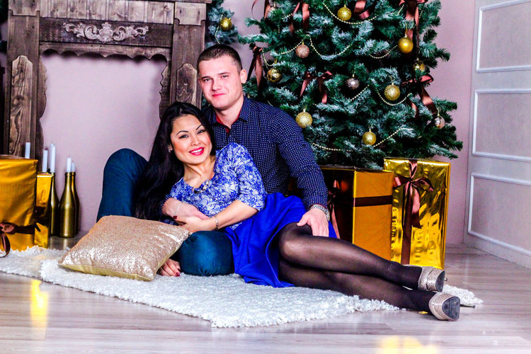 Portrait Of Young Couple On Rug By Decorated Christmas Tree At Home
