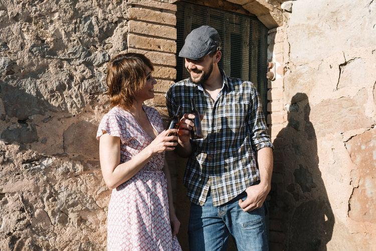 Smiling couple with beer bottles leaning on brick wall