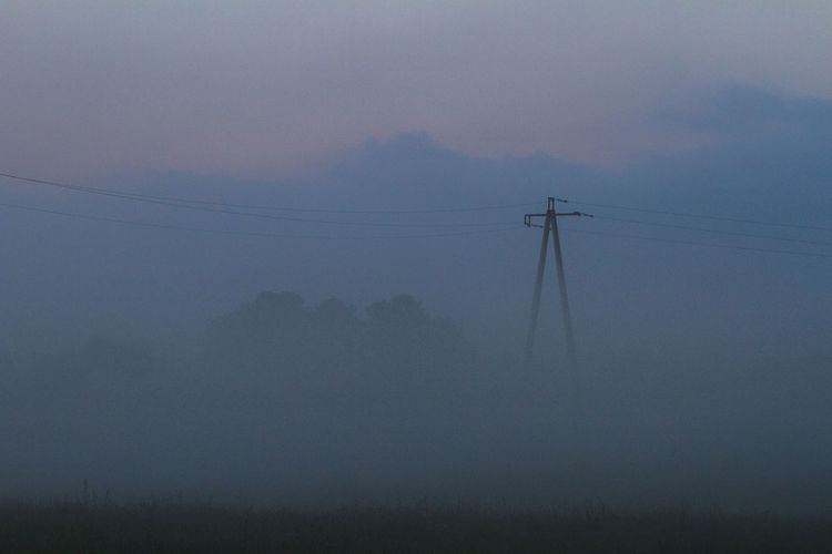Beauty In Nature Cable Connection Day Electricity  Electricity Pylon Field Fog Fuel And Power Generation Landscape Low Angle View Nature No People Outdoors Power Line  Power Supply Scenics Sky Technology Tranquility Tree