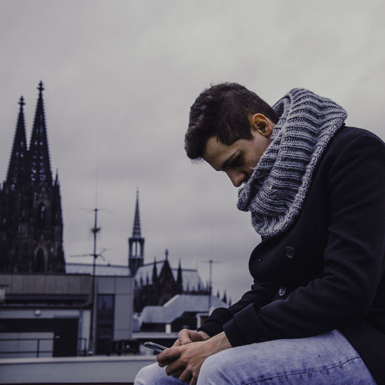 Side view of young man using mobile phone while sitting at building terrace with cologne cathedral in background