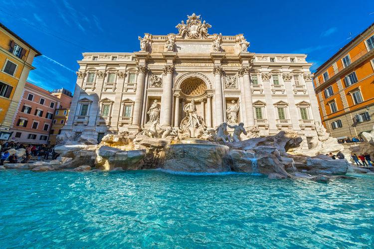 Trevi Fountain Outside Historic Building Against Blue Sky