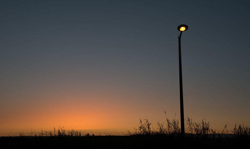 Silhouette Street Light On Field During Sunset