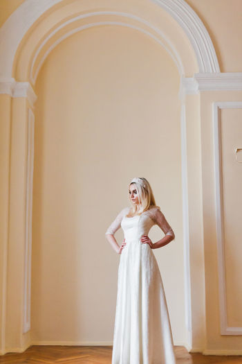 Confident woman in dress standing against wall