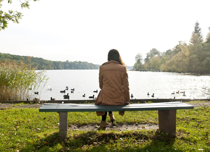 Rear View Of Woman Sitting On Bench At Lakeshore