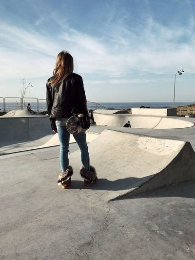 Rear View Of Woman With Skateboard At Skateboard Park