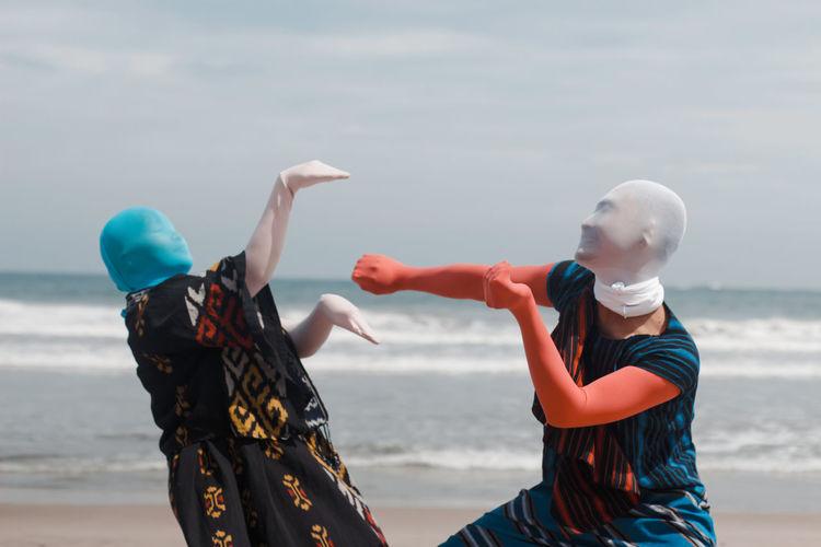 Women standing at beach against sky