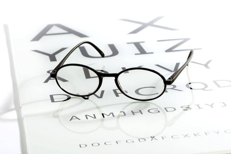 Black oval glasses laying over white glossy eye chart table, sight test optometry concept CorrectiveColor Eyesight Zine Glasses Acuity Chart Eyeglasses  Eyeglasses  Eyesight Helthcare Lenses Medical Optical Optician Optometrist Optometry Sight Test Text Vision