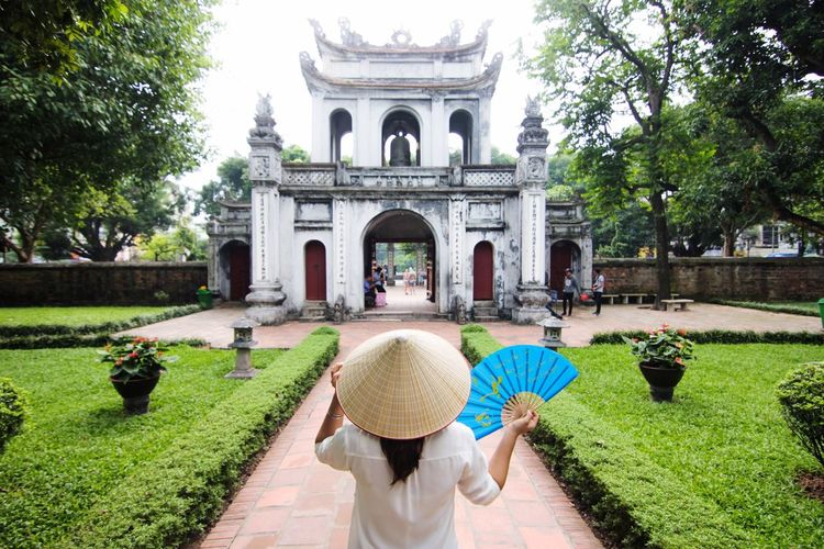 Woman In Asian Style Conical Hat Standing At Temple