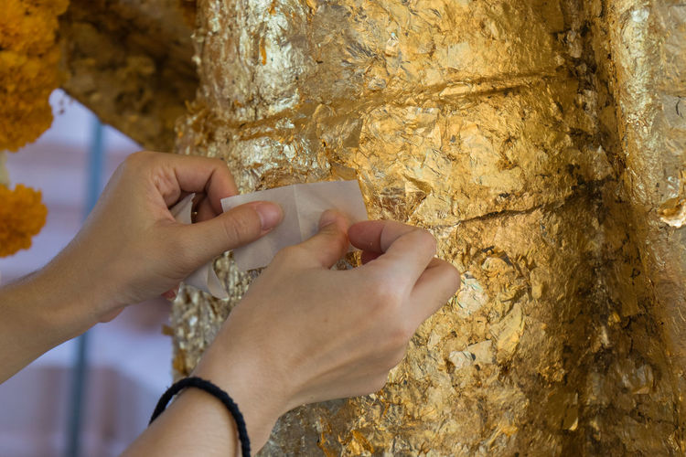 Close-up of hands putting gold foil