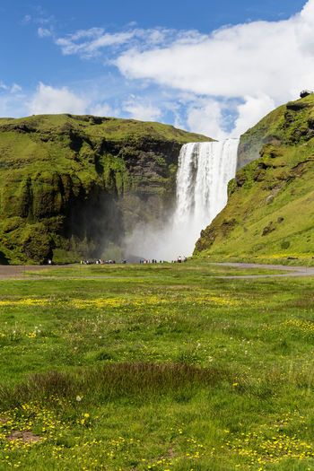 Scenic view of waterfall on field against sky