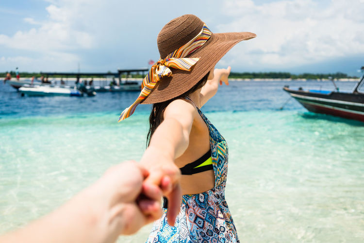 Woman wearing hat holding cropped hand of person while standing on shore against sky