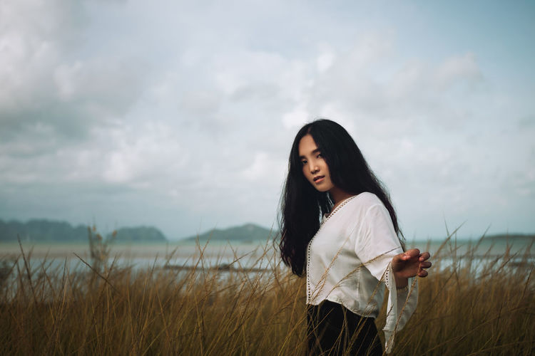 Asian long hair girl in white clothes enjoys life in nature coastal field.