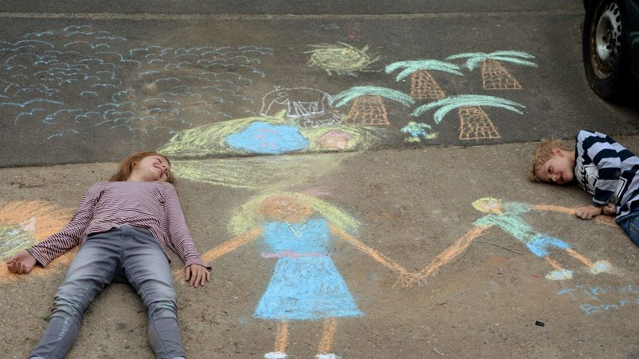 High angle view of siblings lying on chalk drawings at footpath