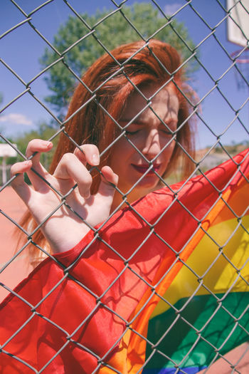 Young Woman With Rainbow Flag Seen Through Chainlink Fence
