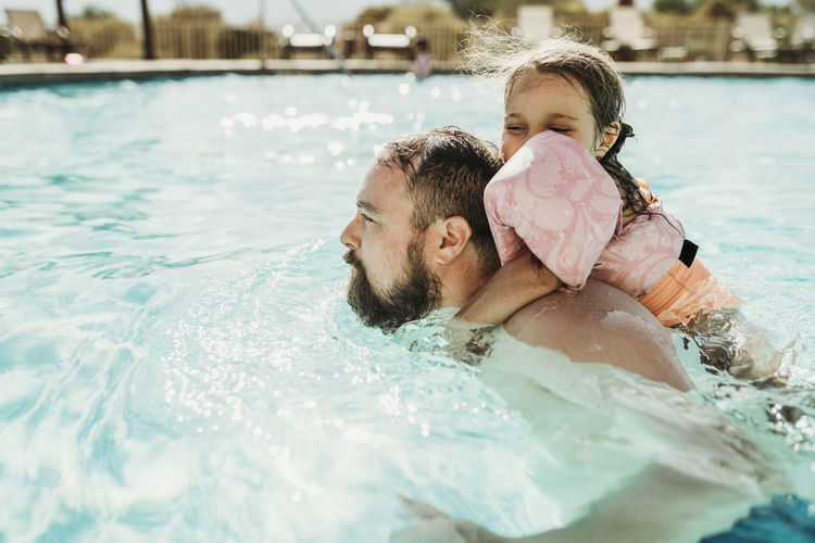 Rear view of father with swimming pool in water
