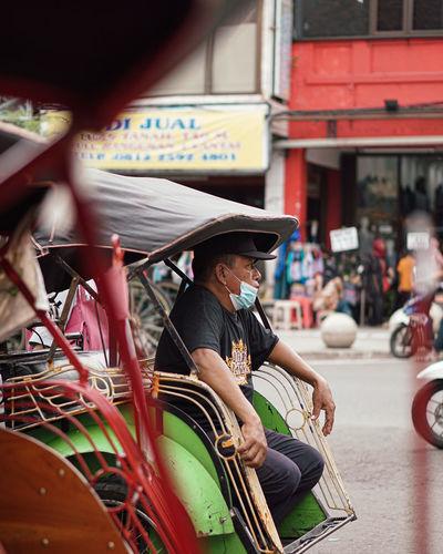 Man wearing mask sitting in jinrikisha
