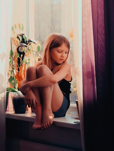Young woman looking away while sitting on window at home