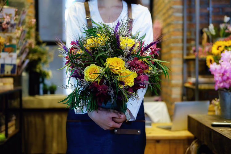 Midsection of florist holding bouquet at flower shop
