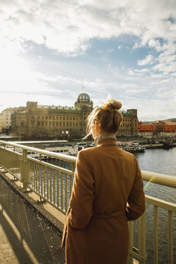 Rear view of woman looking at river in city